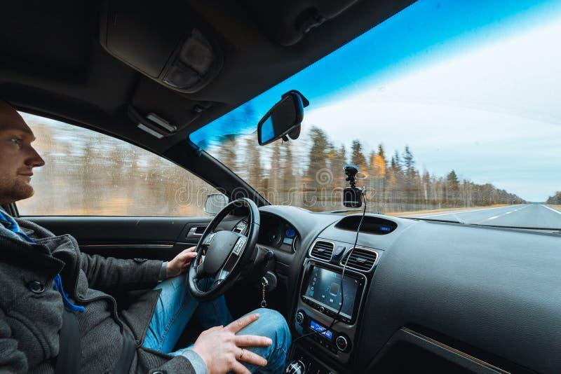 Mężczyzna ręka jedzie samochód przy jesieni drogą między drzewo lasową samiec siedzi wśrodku kontrolnej pojemności audio systemu  zdjęcia royalty free