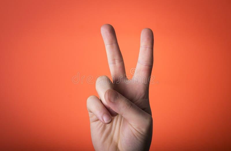 Mężczyzna ręka odizolowywająca na pomarańczowej czerwieni tle obrazy royalty free