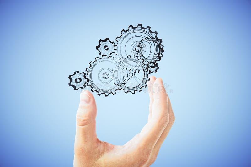 Mężczyzna ręka pokazuje mechanizm przekładnie obraz stock