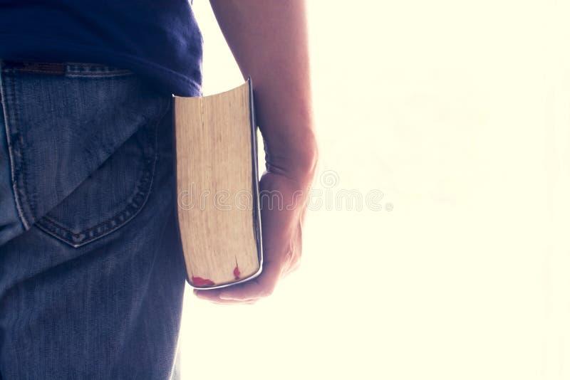 Mężczyzna ręka trzyma biblię odizolowywająca Rocznika kolor To clipp zdjęcie royalty free