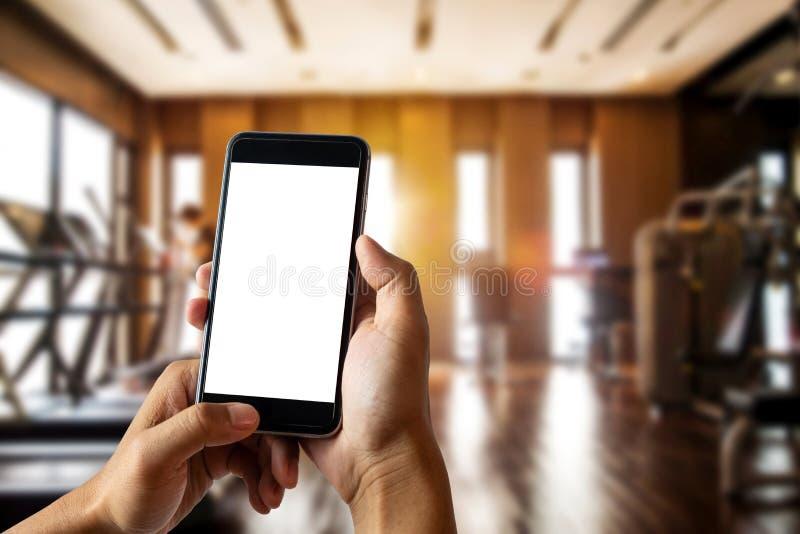 Mężczyzna ręka trzyma mądrze telefonu przyrząd w sprawność fizyczna pokoju obraz stock
