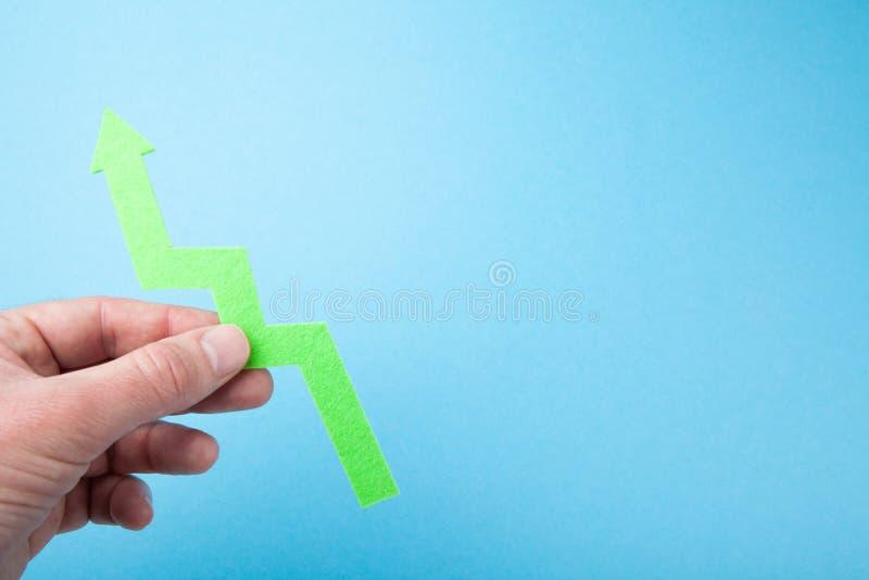 Mężczyzna ręka trzyma strzałę w górę znaka sukces jako niebieska t?a obrazy stock