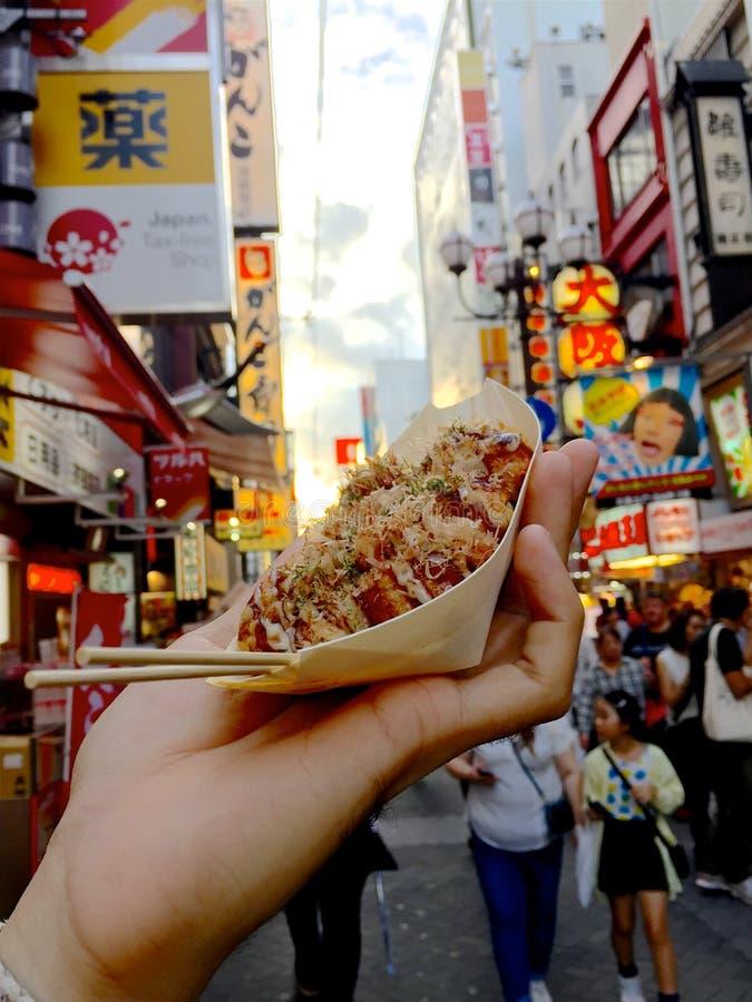 Mężczyzna ręka trzyma Takoyaki talerza w Dotonbori zdjęcie royalty free