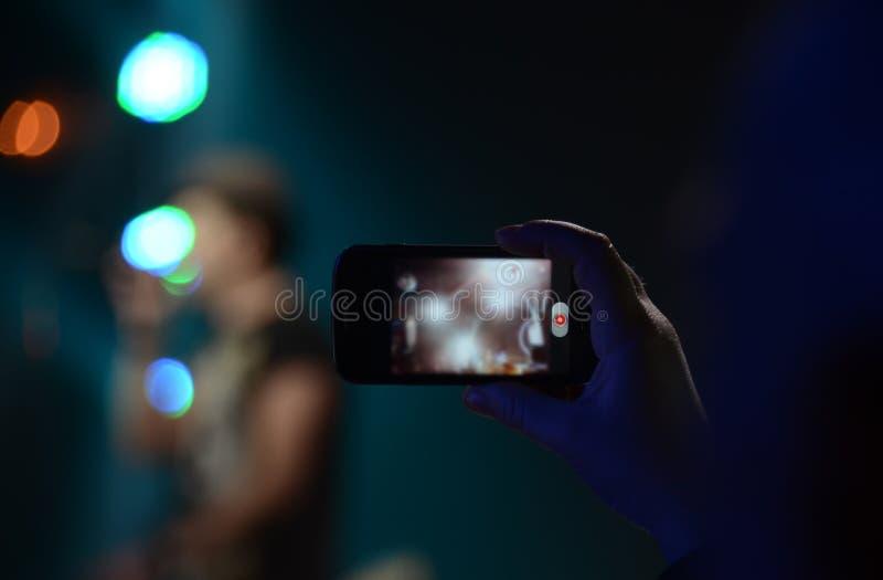 Mężczyzna ręka trzyma telefon i bierze wideo przy rockowym koncertem fotografia stock