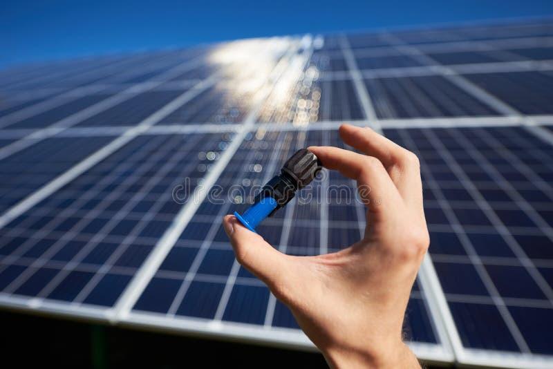Mężczyzna ręka utrzymuje malutkiego szczegół dla słonecznej baterii instalować obrazy royalty free