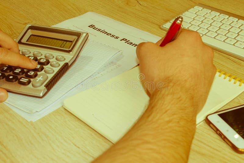 Mężczyzna ręka z kalkulatorem przy miejsca pracy biurem Biznesmena doin obrazy royalty free
