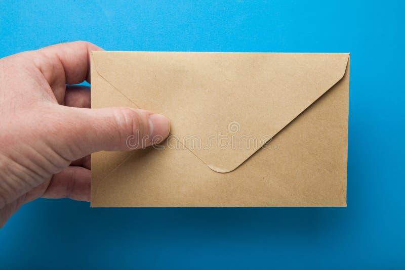 Mężczyzna ręki chwyta koperta na błękitnym tle obraz royalty free