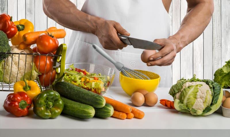 Mężczyzna ręki kucharz robi omelette, bije śmignięć jajka, na kuchni obraz stock