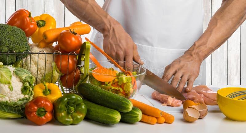 Mężczyzna ręki kucharza rżniętego kurczaka kurczaka mięsna pierś i sałatka na ki zdjęcia royalty free