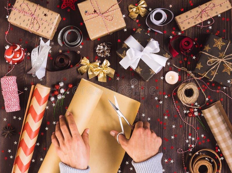 Mężczyzna ręki mienia rolka Kraft opakunkowy papier z nożycami dla tnącego kocowań bożych narodzeń prezenta pudełka fotografia stock
