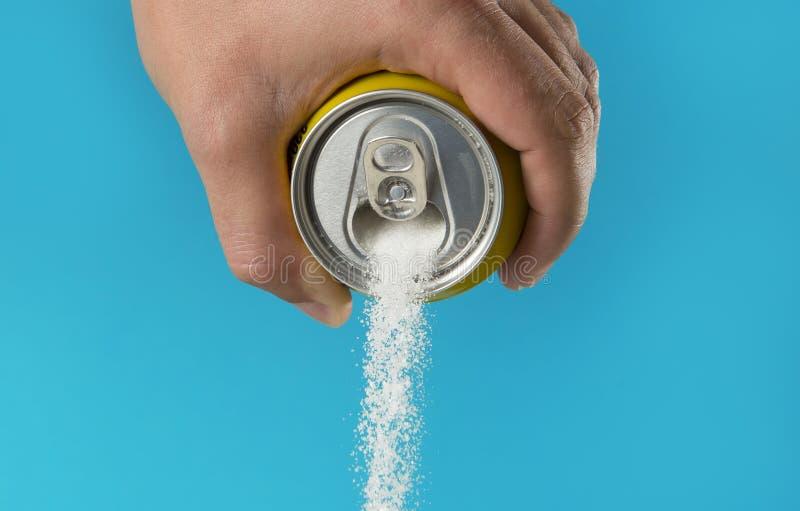 Mężczyzna ręki mienie odświeża napój może dolewanie cukrowy strumień w cukierki i kaloriach zawartości napoje sody i energii zdjęcie stock