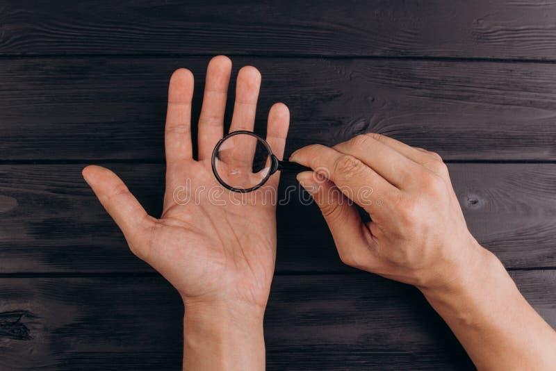 Mężczyzna rÄ™ki na nieociosanym czarnym biurku trzyma powiÄ™kszać - szkÅ'o odcisk palca egzamin palmowy zbliżenie zdjęcie stock