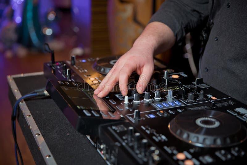 Mężczyzna ręki naciskają guziki na DJ pilocie, ja robią muzyce DJ ręki przy muzycznym melanżerem przy przyjęciem - bawić się niek zdjęcie royalty free