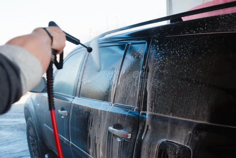Mężczyzna ręki obmycie brudny SUV wysokość naciska obmyciem Touchless samochodowego obmycia samoobsługa w na wolnym powietrzu Con fotografia stock