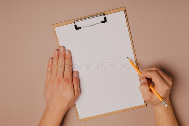 Mężczyzna ręki pisze na klamerki desce na szarym tle zdjęcia royalty free