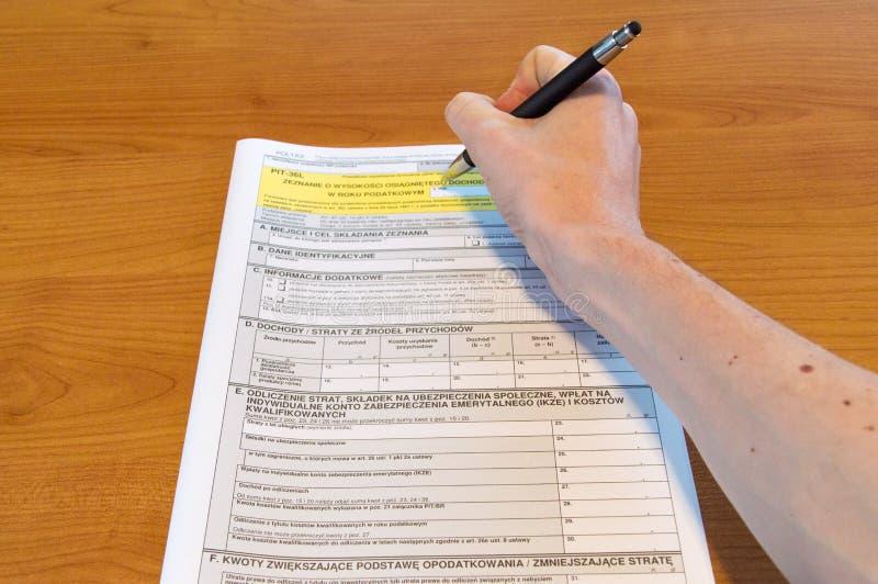 Mężczyzna ręki plombowania połysku podatku dochodowego indywidualna forma PIT-36L fotografia royalty free