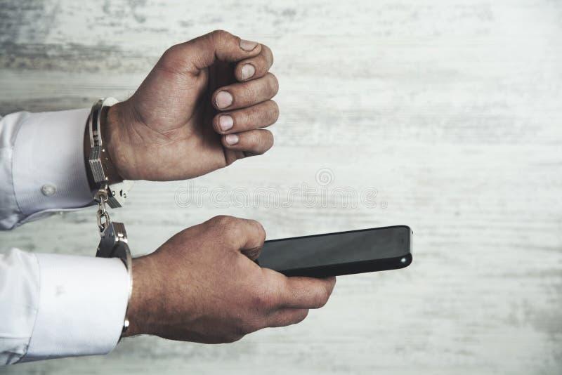 Mężczyzna ręki telefon i kajdanki obrazy royalty free