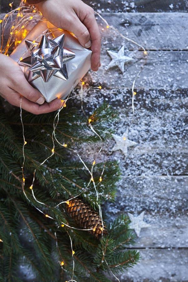 Mężczyzna ręki trzyma boże narodzenie prezenta pudełko na drewnianym błękicie wsiadają z c zdjęcia stock