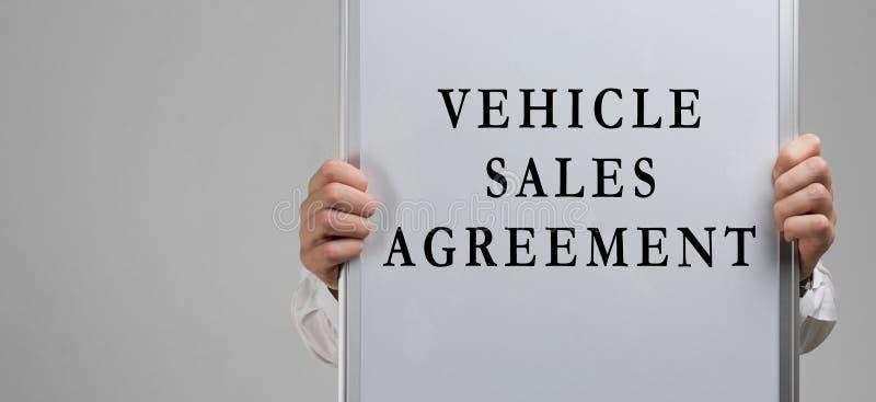 Mężczyzna ręki trzyma plakat z wpisową pojazd sprzedaży zgodą odizolowywającą na lekkim tle obraz stock