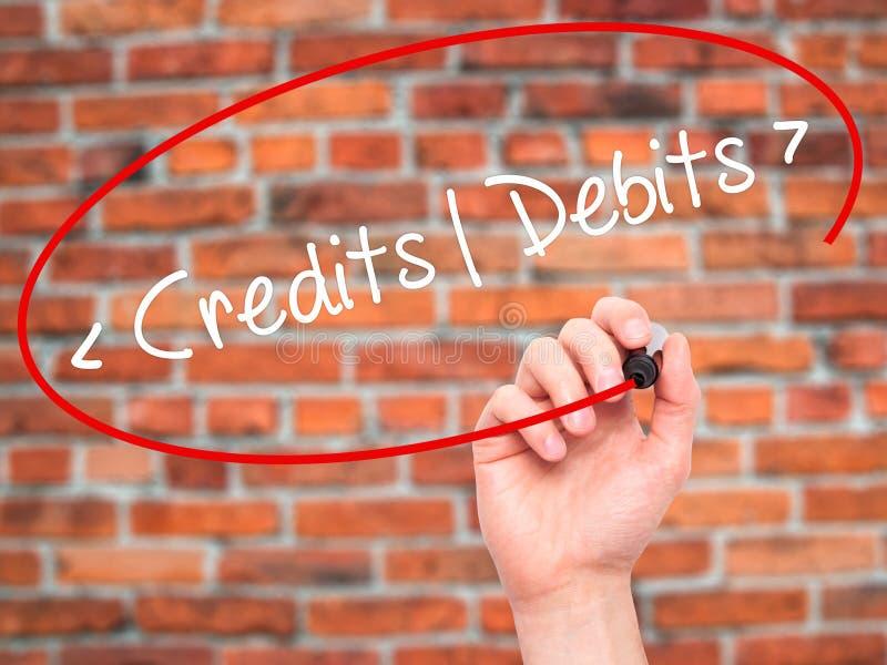 Mężczyzna ręki writing kredyty - debety z czarnym markierem na projekta sc obrazy stock
