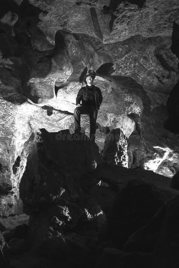 Mężczyzna rekonesansowa ogromna jama Przygoda podróżnicy ubierali kowbojskiego kapelusz i plecaka, skórzana kurtka czarny i biały fotografia stock