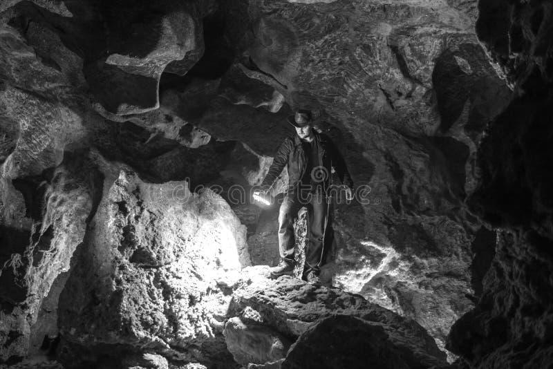 Mężczyzna rekonesansowa ogromna jama Przygoda podróżnicy ubierali kowbojskiego kapelusz i plecaka, skórzana kurtka czarny i biały obrazy stock