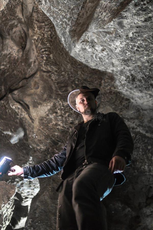 Mężczyzna rekonesansowa ogromna jama Przygoda podróżnicy ubierali kowbojskiego kapelusz i skórzaną kurtkę ekstremum, turystyczna  zdjęcie royalty free