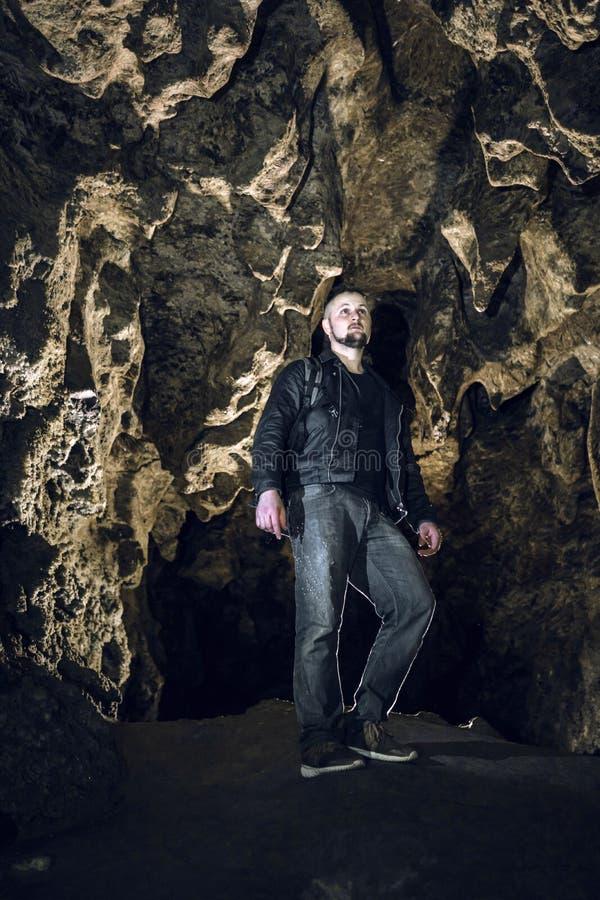 Mężczyzna rekonesansowa ogromna jama Przygoda podróżnicy ubierali skórzaną kurtkę ekstremum, niebezpieczeństwo hobby, turystyczna fotografia stock