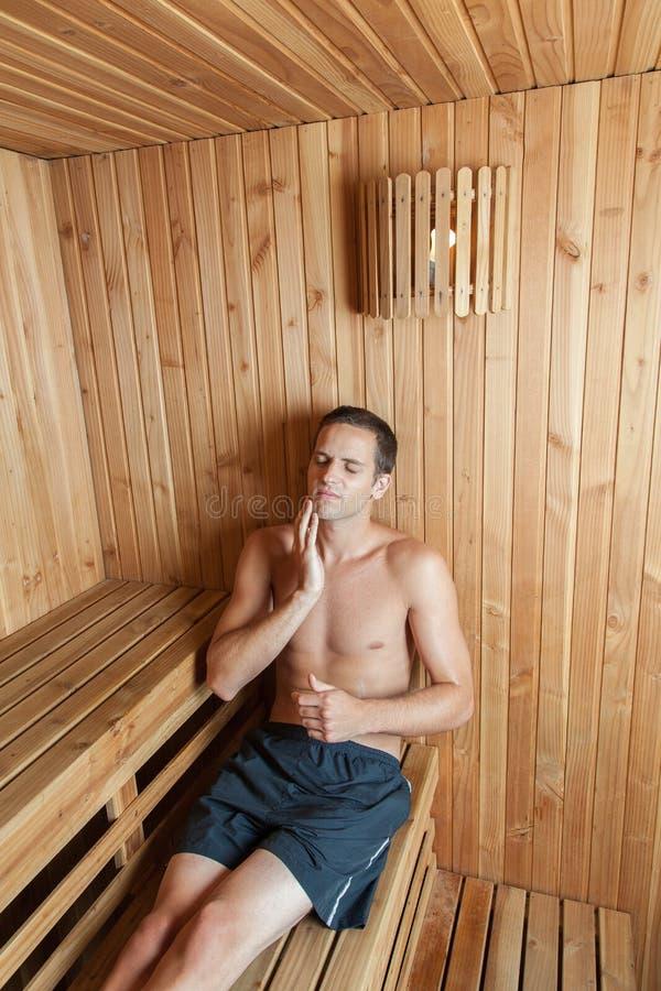 Mężczyzna relaksujący wśrodku sauna obraz stock