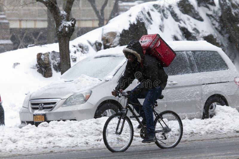Mężczyzna robi dostawie na rowerze w śnieżnej burzy obrazy royalty free