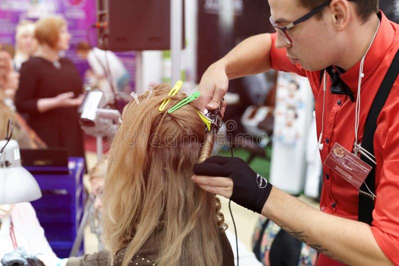 Mężczyzna robi fryzurze dla dziewczyny pokazywać nowych trendy wewnątrz zdjęcie stock