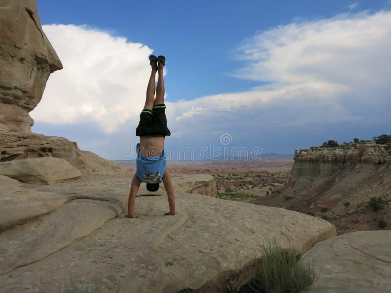 Mężczyzna robi Handstand na falezach z pole krajobrazem w pustyni obraz stock