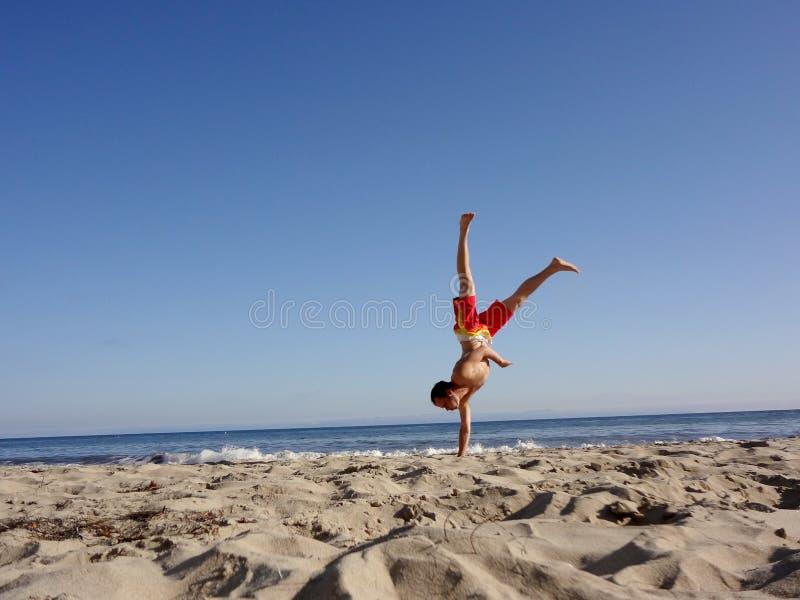 Mężczyzna robi jeden wręczającemu Handstand na plaży obraz royalty free