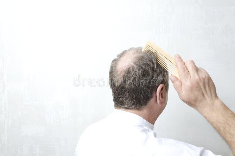 Mężczyzna robi jego włosy z drewnianą gręplą Mężczyzna z łysym plecy głowa Pojęcie włosiana strata Opróżnia przestrzeń dla twój t fotografia stock