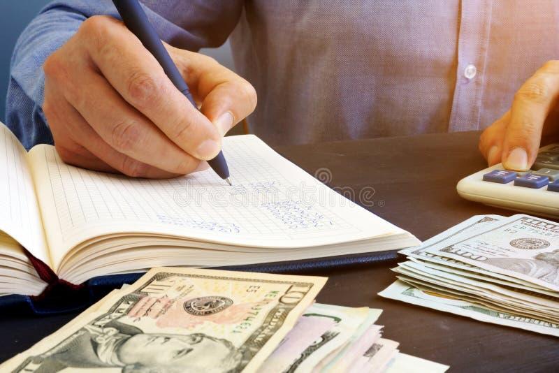 Mężczyzna robi pieniężnym obliczeniom w notepad księgowość obraz royalty free