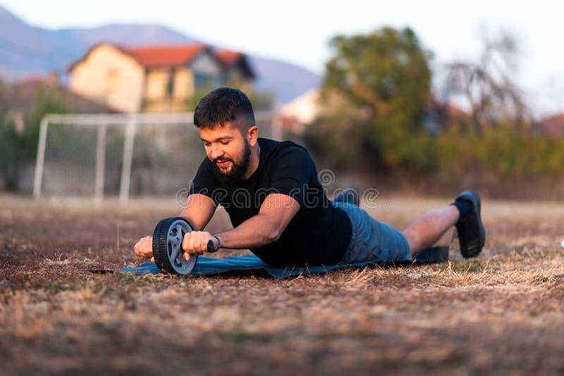Mężczyzna robi treningowi z ab rolownikiem obrazy royalty free
