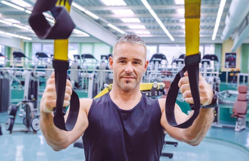 Mężczyzna robi zawieszenia szkoleniu z sprawności fizycznych patkami fotografia stock
