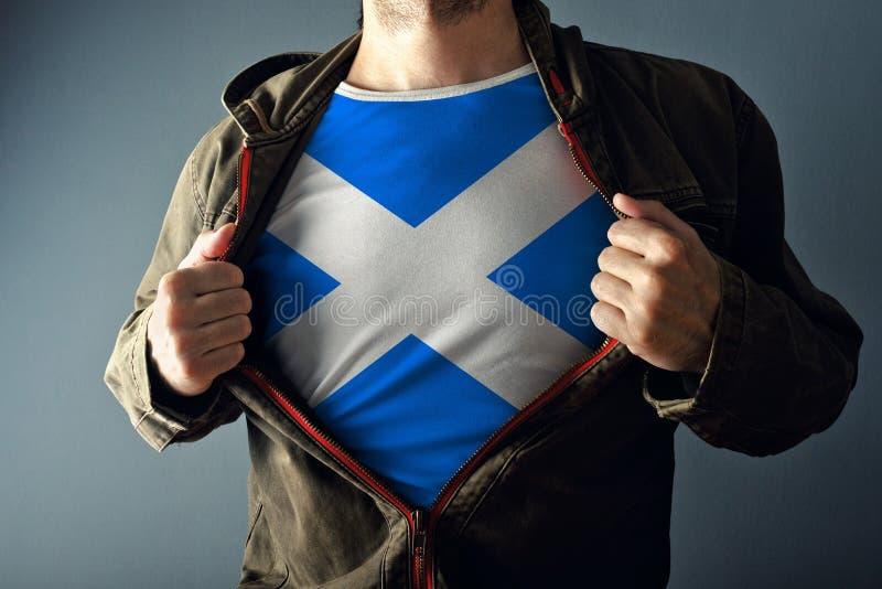 Mężczyzna rozciągania kurtka wyjawiać koszula z Szkocja flaga zdjęcie royalty free