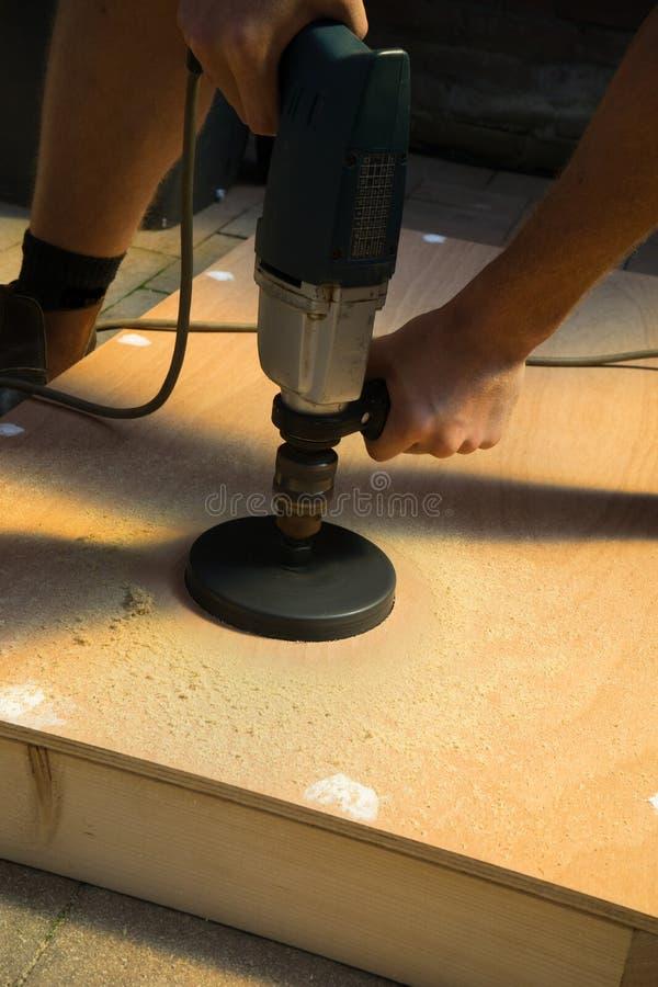 Mężczyzna rozcięcia dziury DIY cornhole deski projekt zdjęcia stock