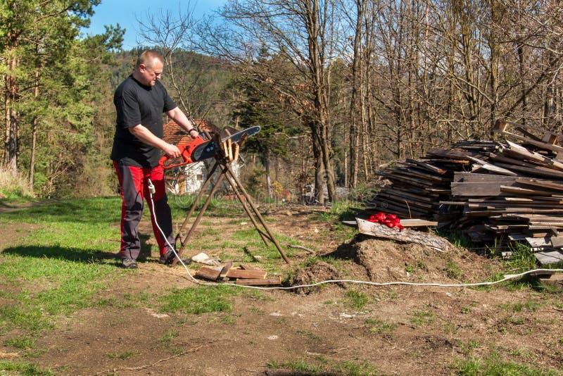 Mężczyzna rozcięcie z elektrycznym łańcuszkowym saw Praca na gospodarstwie rolnym Drewniany przygotowanie dla ogrzewać Woodcutter obrazy royalty free