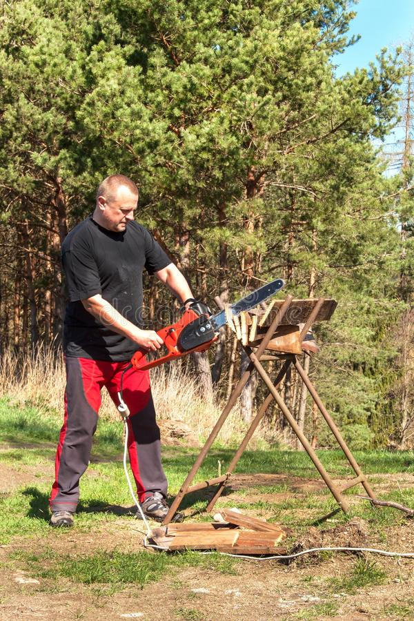 Mężczyzna rozcięcie z elektrycznym łańcuszkowym saw Praca na gospodarstwie rolnym Drewniany przygotowanie dla ogrzewać Woodcutter obraz royalty free