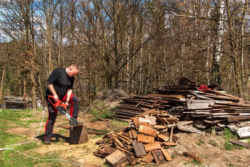Mężczyzna rozcięcie z elektrycznym łańcuszkowym saw Praca na gospodarstwie rolnym Drewniany przygotowanie dla ogrzewać Woodcutter obrazy stock