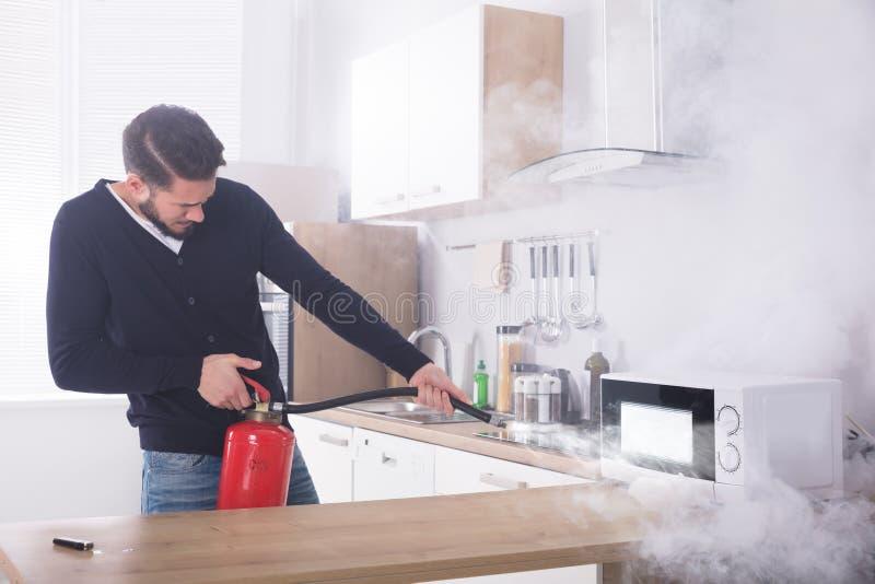 Mężczyzna Rozpyla Pożarniczego gasidło Na mikrofala piekarniku obraz royalty free