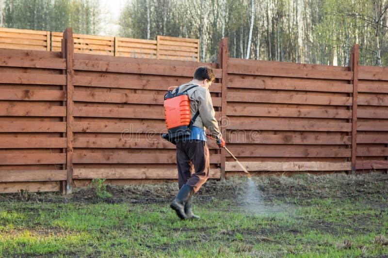 Mężczyzna rozpyla trawy z herbicydem plecakowa natryskownica obrazy royalty free