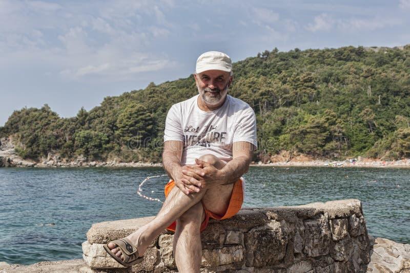 Mężczyzna rzuca jego stopę na stopie dojrzały wiek siedzi na skałach zdjęcia royalty free