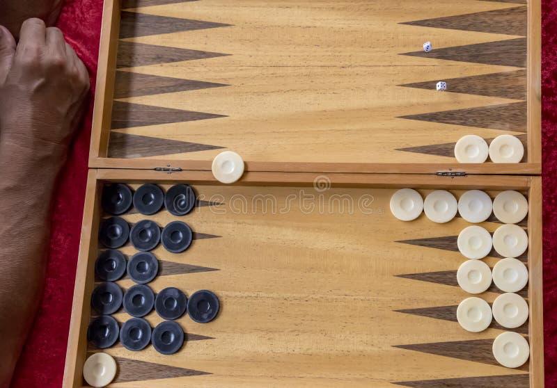 Mężczyzna rzuca kostki do gry podczas gdy bawić się bacgammon zdjęcia royalty free
