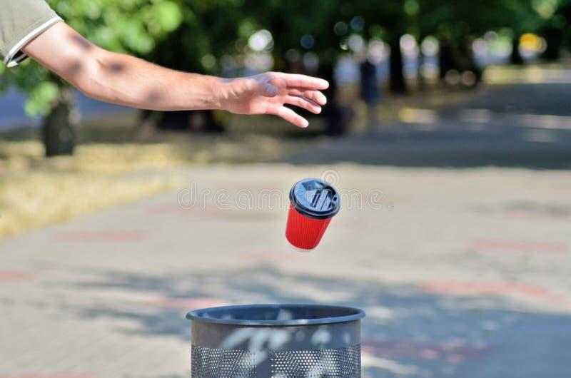 Mężczyzna rzucił czerwoną papierową filiżankę na kawę w śmietniku, kubek leci w powietrzu, na tle zielonych drzew i ulicz obrazy royalty free