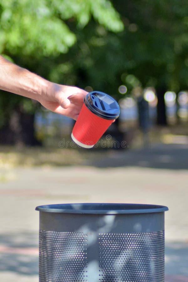 Mężczyzna rzucił czerwoną papierową filiżankę na kawę w śmietniku, kubek w locie, tło zielonych drzew, pionowo obraz stock