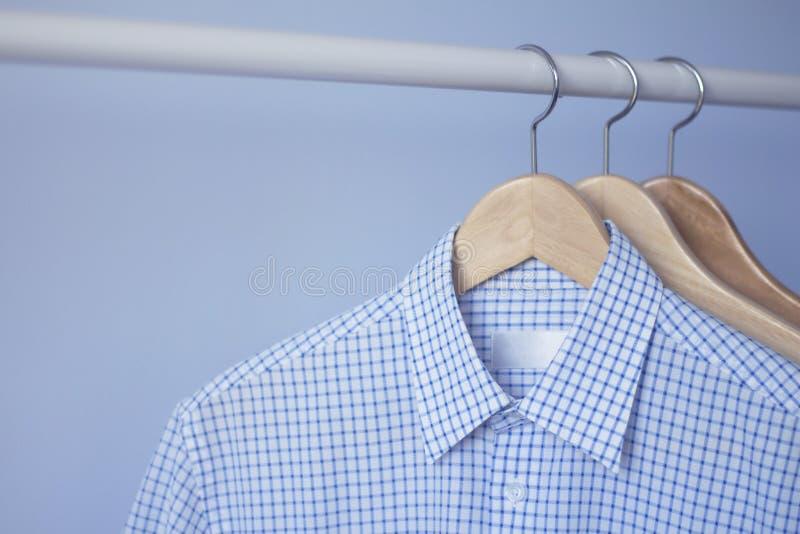 Mężczyzna ` s błękitna w kratkę koszula na drewnianym wieszaku fotografia royalty free