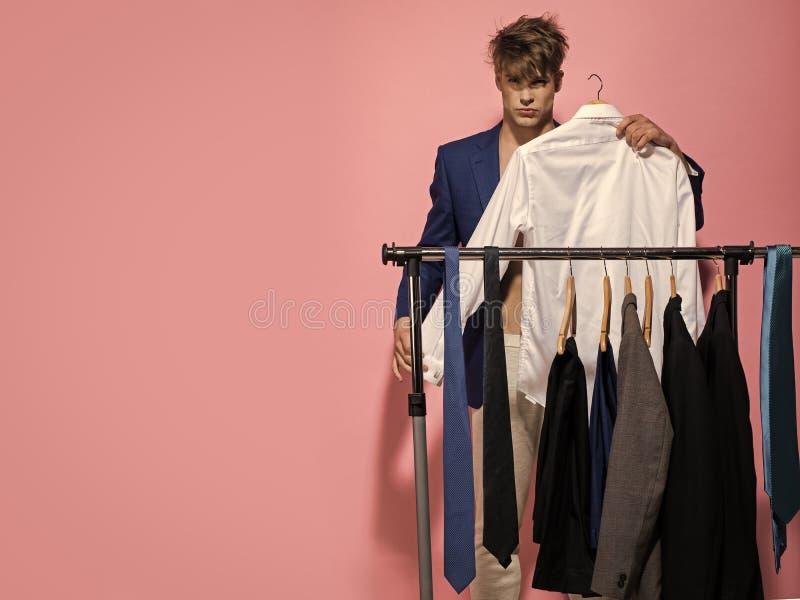 Mężczyzna ` s garderoba Macho wybiera koszula w garderobie na różowym tle obraz stock